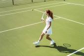 Fotografia bella donna sul bianco sportswear e occhiali da sole, giocare a tennis sul campo