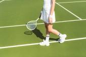 částečný pohled tenistka v bílém oblečení s raketou na tenisový kurt