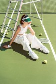 mladá žena v módní bílé oblečení a kryt sedí na tenisový kurt s pálky a míčky