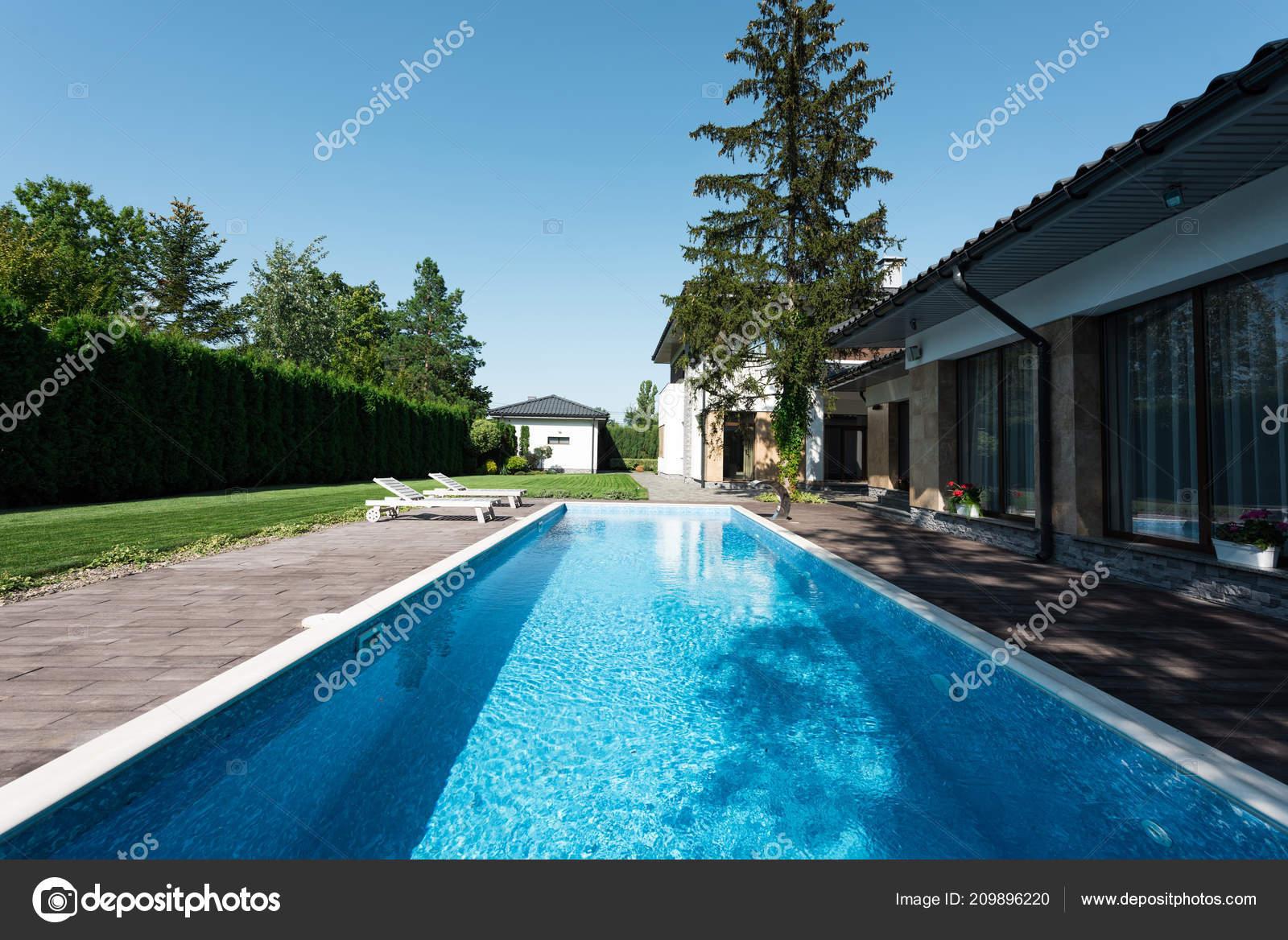 Weergave van moderne huis zwembad met ligbedden u stockfoto y
