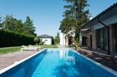 pohled na dům, zahradu a bazén s lehátky pro relax