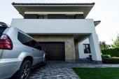 Fotografie fasáda z nového moderního domu s autem na parkoviště