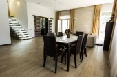 Photo interior view of modern dining room with table, chairs and stairs