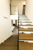 interior view of modern stairs with glass railings to living room
