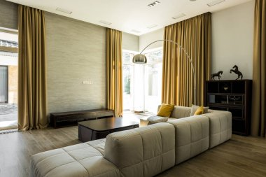 interior of empty modern living room with sofa and big windows with curtains
