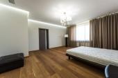 Fotografia interno della camera da letto moderna con grande finestra e materasso sul letto