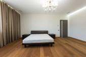 Fotografia interno della camera da letto vuota con tende e materasso sul letto