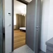 Fotografia elegante camera da letto con letto matrimoniale, vista dalla porta del bagno