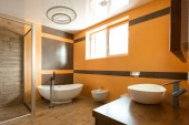 Fotografia interior of bathroom in orange and white colors with bathtube, sink and bidet