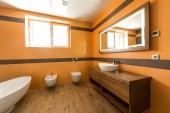 interiér moderní koupelny v oranžové a bílé barvy