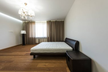 interior of empty bedroom with curtains on big window and mattress on bed
