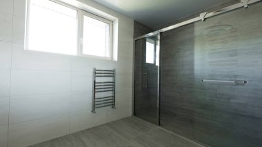 interior of empty bathroom with glass shower in grey color