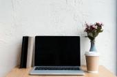 Fotografia computer portatile con lo schermo in bianco e tazza di carta sulla tavola di legno