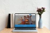 přenosný počítač s couchsurfing stránky na obrazovce, knihy a květiny ve váze na dřevěný stůl