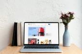 přenosný počítač s ebay stránky na obrazovce, knihy a květiny ve váze na dřevěný stůl