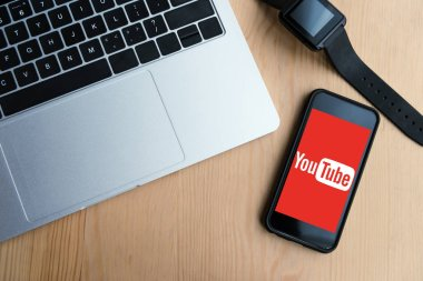 top view of laptop, smartwatch and smartphone with youtube website on screen