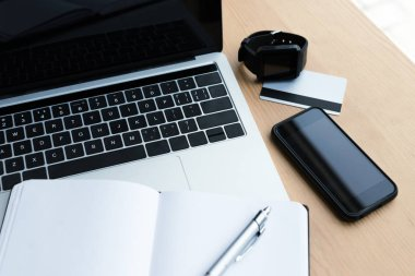 high angle view of laptop, smartwatch, smartphone, credit card and blank notebook with pen on  table