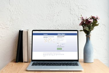 laptop with facebook website on screen, books and flowers in vase on wooden table
