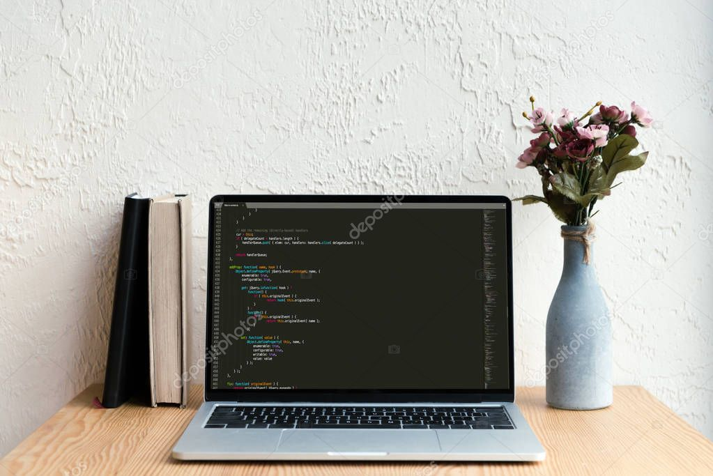 laptop with html code on screen, books and flowers in vase on wooden table