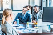 smiling multicultural businessmen looking at colleague in office
