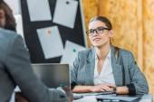 usmívající se multikulturní podnikatelka a podnikatel mluví v úřadu