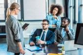 multikulturní podnikatelé při pohledu na podnikatelka s tabletem v úřadu