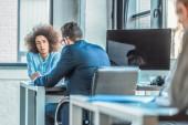 multikulturní podnikatelé sedí u stolu v kanceláři