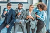 multikulturní podnikatelé s kávou, noviny a smartphone v úřadu