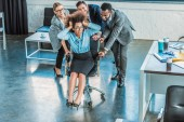 Fotografie multicultural businesspeople having fun and racing colleague on chair in office