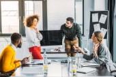 Fotografie multikulturní mladí podnikatelé na schůzce v kanceláři