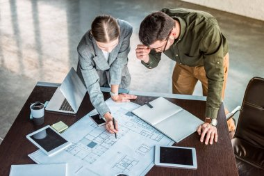 high angle view of businesswoman showing something at blueprint to businessman
