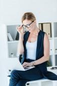 Konzentrierte Geschäftsfrau mit Brille sitzt am Tisch und arbeitet im Büro am Laptop