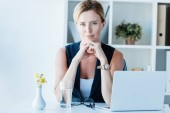 portrait of adult businesswoman looking at camera and sitting at table with laptop in office