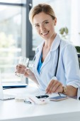 Fotografie smiling female doctor holding glass of water and taking pill at table in office