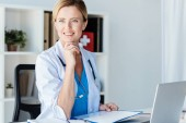 smiling female doctor with stethoscope looking away at table with clipboard and laptop in office