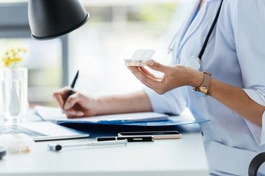 cropped image of female doctor writing in clipboard and holding pills at table in office