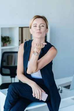 adult businesswoman holding smartphone and blowing air kiss in office