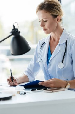 confident adult female doctor in white coat with stethoscope writing in clipboard at table in office