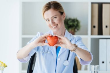 Selective focus of female doctor in white coat showing heart symbol at table in office stock vector