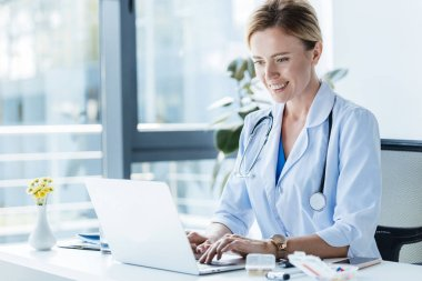 smiling adult female doctor in white coat using laptop at table in office