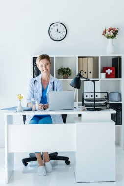 attractive adult female doctor looking at camera and sitting at table with laptop in office