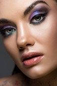beautiful young woman with glitter eyeshadows and makeup, isolated on grey