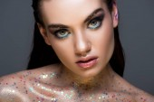 Fotografie glamorous girl with glitter on body and makeup looking at camera, isolated on grey