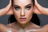Fotografie glamorous woman with makeup and glitter on body, isolated on grey