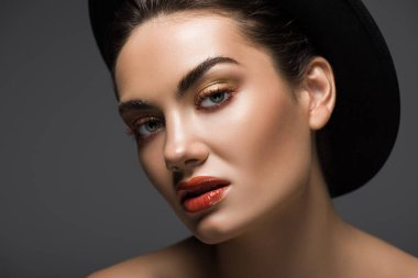 elegant model with makeup posing in stylish felt hat, isolated on grey