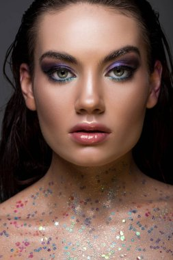 beautiful glamorous girl posing with glitter on body and looking at camera, isolated on grey