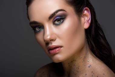 fashionable young woman posing with glitter makeup, isolated on grey