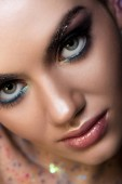 Fotografie Close up of young woman with glitter makeup looking at camera