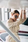 mladá žena v sluneční brýle a bunda při pohledu na fotoaparát u letadla