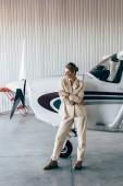 Fotografie modische Frau mit Sonnenbrille und Jacke posiert in der Nähe von Flugzeugen im hangar